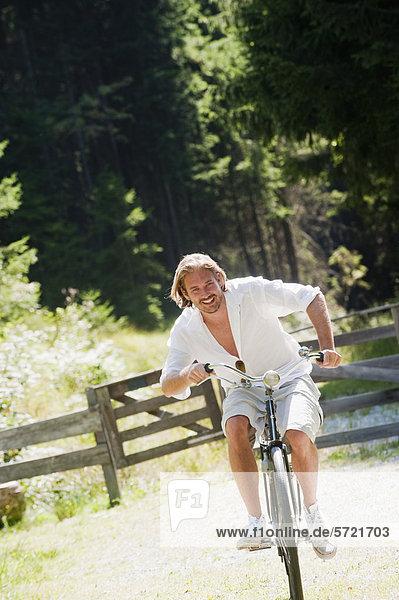 Österreich  Salzburger Land  Mittelerwachsener Mann mit altem Fahrrad