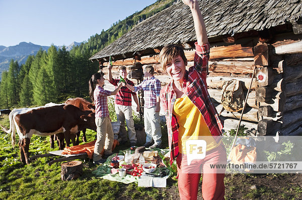 Österreich  Salzburger Land  Männer und Frauen beim Picknick in der Nähe der Almhütte bei Sonnenuntergang