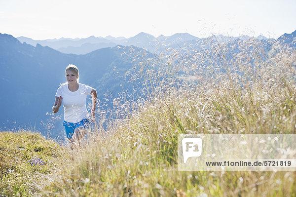Österreich  Salzburger Land  Junge Frau beim Laufen auf der Alm