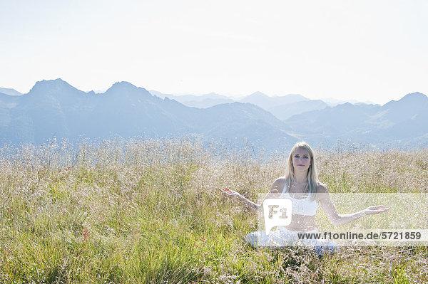 Österreich  Salzburger Land  Junge Frau auf der Alm sitzend und meditierend