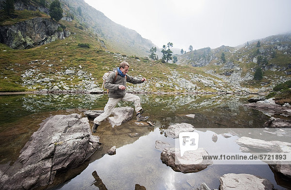 Österreich  Steiermark  Mittelerwachsener Mann beim Springen am Spiegelsee