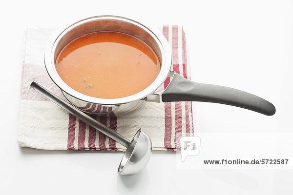 Tomatensuppe im Kochtopf mit Schöpfkelle und Serviette auf weißem Grund