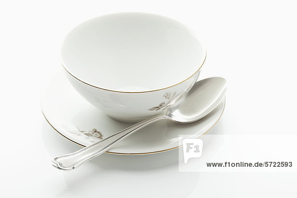 Leere Schale und Teller mit Löffel auf weißem Hintergrund