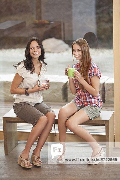 Junge Frauen sitzen auf der Bank mit Tasse  lächelnd