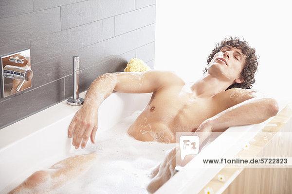 Junger Mann beim Baden in der Badewanne