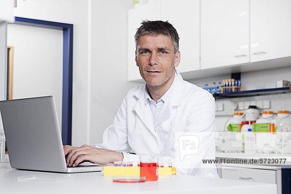 Germany  Bavaria  Munich  Scientist with laptop in laboratory  portrait