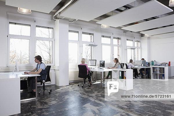 Männer und Frauen  die am Computer im Büro arbeiten