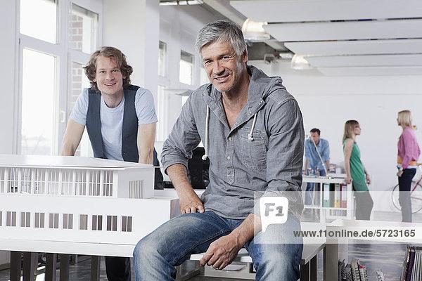 Männer mit Architekturmodell im Büro  Kollegen sprechen im Hintergrund