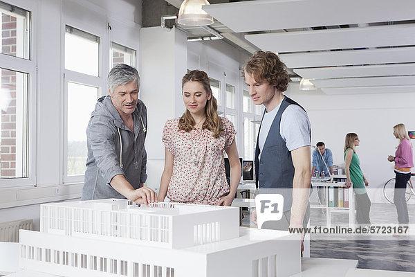 Mann erklärt Kollegen das Architekturmodell