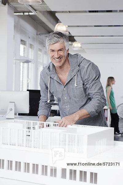 Mann stehend mit Architekturmodell im Büro