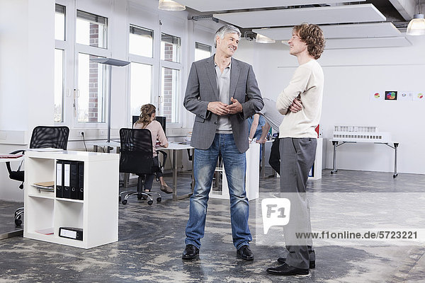 Männer diskutieren  Kollegen im Hintergrund