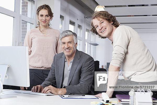Männer und Frauen mit Computer im Büro  lächelnd  Porträt