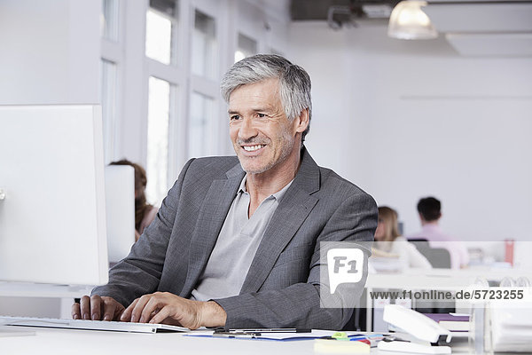 reifer Mann mit Computer  Kollegen im Hintergrund