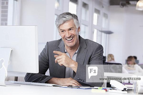 Reifer Mann lächelt  Kollegen arbeiten im Hintergrund