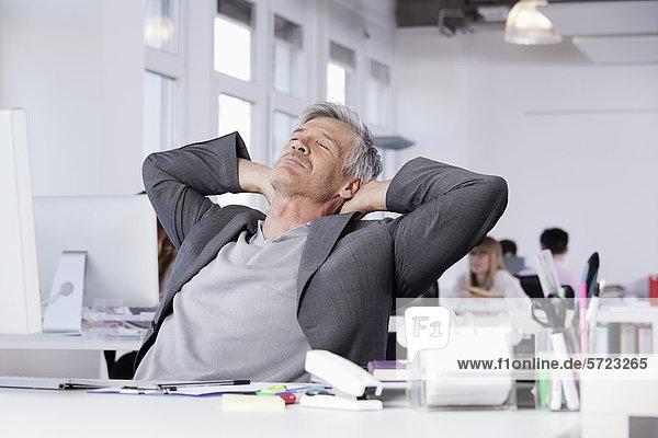 Der reife Mann ruht sich aus  die Kollegen arbeiten im Hintergrund.