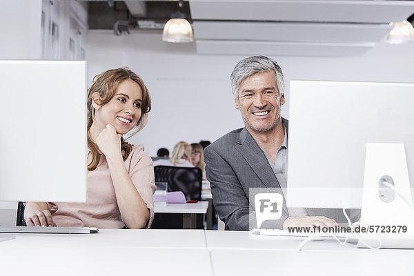 Mann und Frau mit Computer im Büro  lächelnd