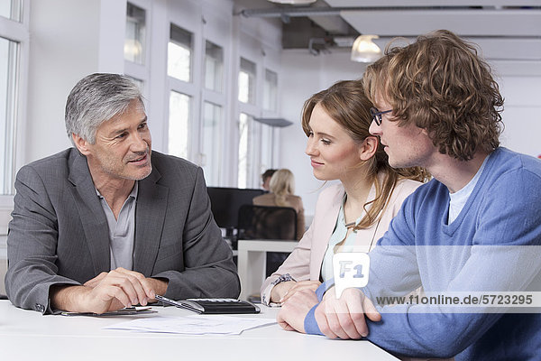 Männer und Frauen diskutieren bei Tisch