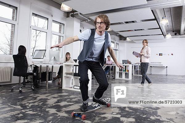 Man Skate Boarding im Büro  während die Kollegen im Hintergrund arbeiten.