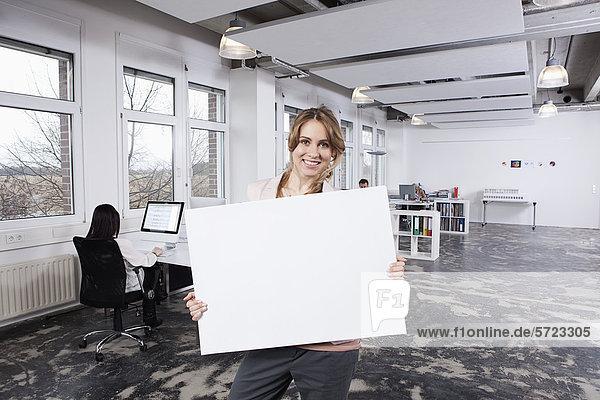 Frau mit Plakat  Kollegen im Hintergrund