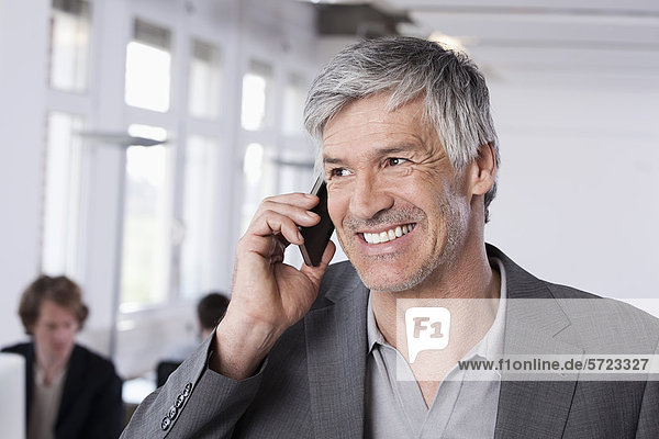 Mature man on mobile phone  colleagues working in background