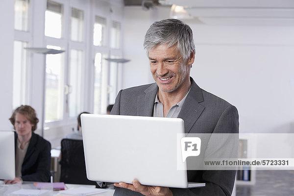 Erwachsener Mann mit Laptop  Kollegen  die im Hintergrund arbeiten