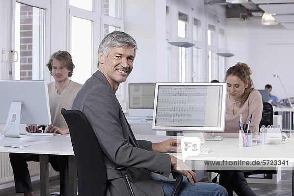 Mature man smiling  colleagues working in background