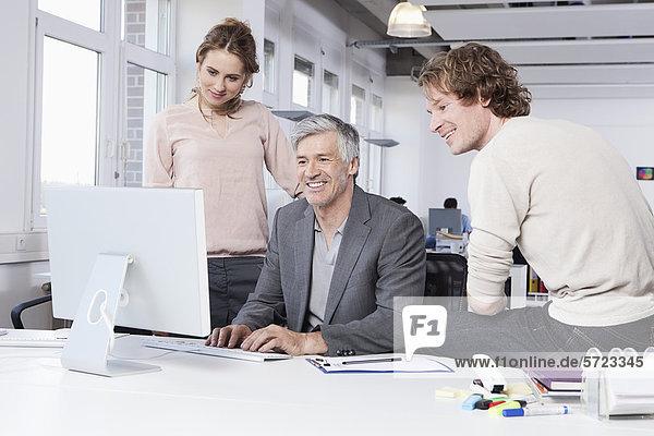 Männer und Frauen  die den Computer im Büro benutzen  lächelnd