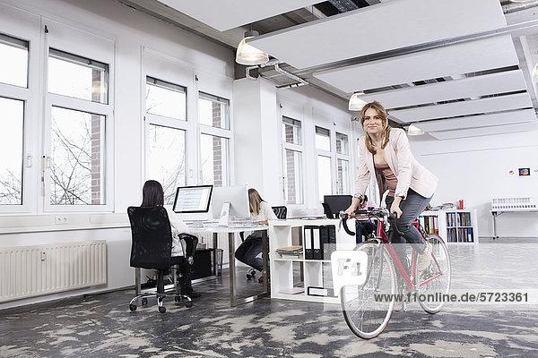 Frau beim Radfahren im Büro  während Kollegen arbeiten
