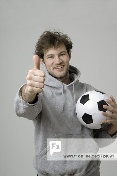 Junger Mann hält Fußball und zeigt Daumen nach oben