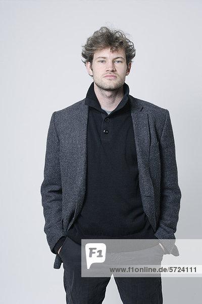 Mann mit grauem Mantel auf weißem Grund stehend