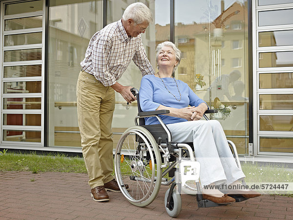 Senior Mann schiebt Frau im Rollstuhl