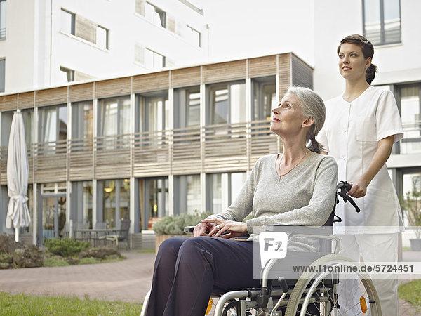 Hausmeisterin schiebt ältere Frauen im Rollstuhl