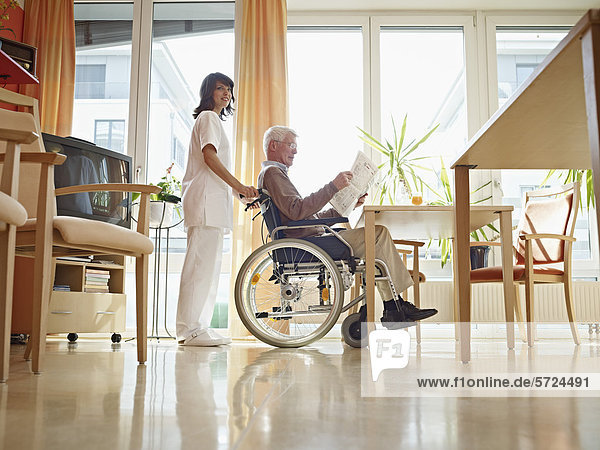 Älterer Mann beim Zeitungslesen im Rollstuhl  Hausmeister neben ihm stehend