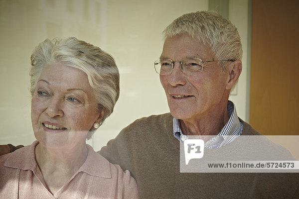 Deutschland  Köln  Seniorenpaar schaut weg  lächelnd
