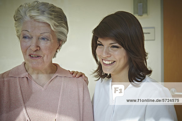 Seniorenfrauen und Betreuerinnen  die im Pflegeheim wegschauen  lächelnd