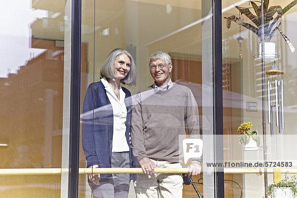 Deutschland  Köln  Seniorenpaar schaut durchs Fenster  lächelnd