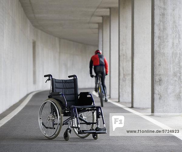 Österreich  Mondsee  Junger Mann auf Mountainbike mit Rollstuhl im Vordergrund