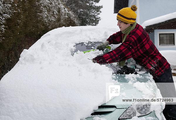 Österreich  Junger Mann beim Putzen von Schnee am Auto