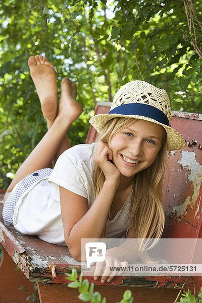 Österreich  Teenagermädchen entspannt auf Bank im Garten  Portrait