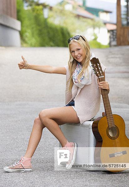 Österreich  Teenagerin mit Rollgepäck und Gitarre  Portrait Österreich, Teenagerin mit Rollgepäck und Gitarre, Portrait