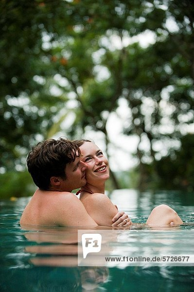 A couple embrace while bathing in a pool