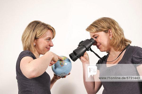 Zwillingsschwestern mit Fernglas und Globus