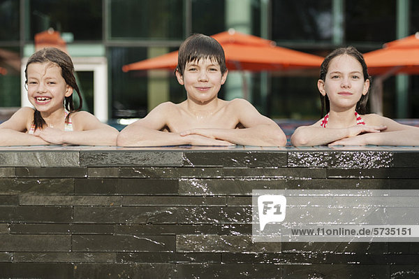 Geschwister  die sich am Rand des Swimmingpools nebeneinander lehnen  lächelnd  Portrait