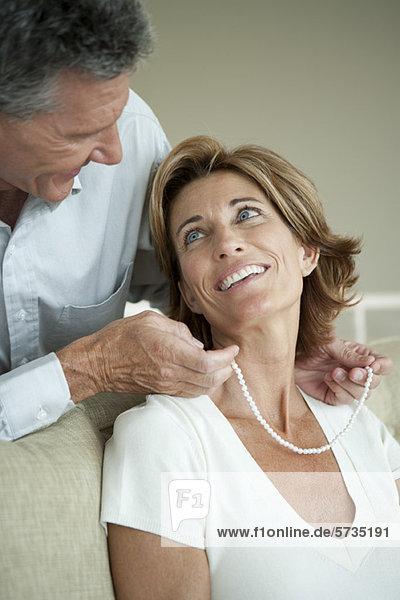 Reifer Mann schenkt Frau eine Perlenkette