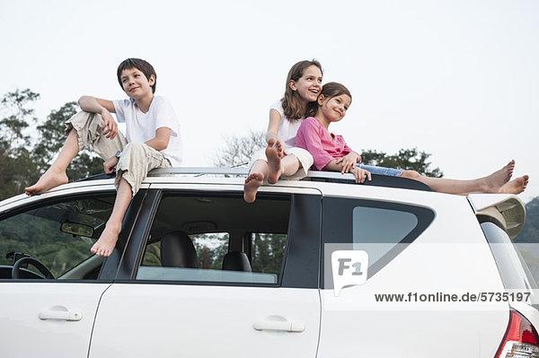 Geschwister sitzen zusammen auf dem Autodach