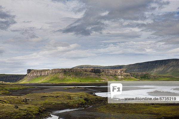 Iceland  stream running through lava field  basalt cliffs in the distance