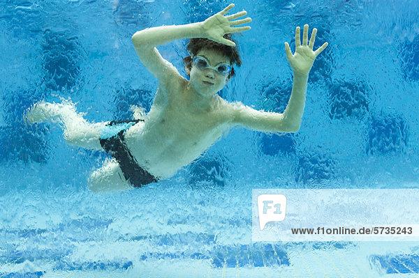 Junge schwimmt unter Wasser im Schwimmbad