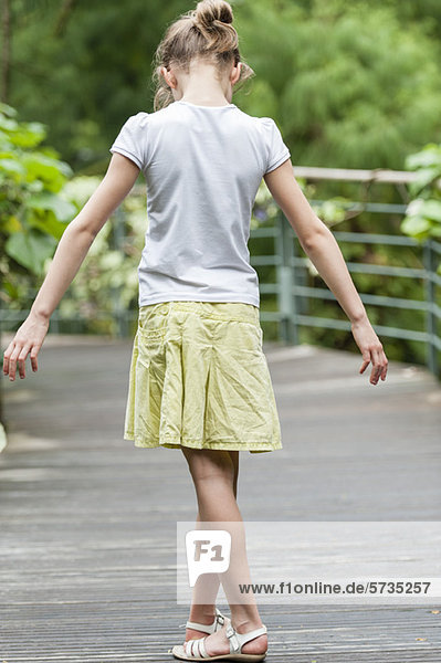 Mädchen in Gedanken versunken  auf ihre Füße schauend
