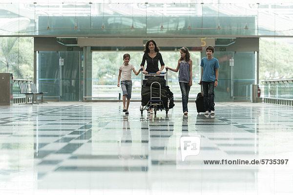 Familie schiebt Gepäckwagen in der Flughafenlobby Familie schiebt Gepäckwagen in der Flughafenlobby