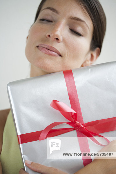 Frau umarmt Geschenk  Augen geschlossen